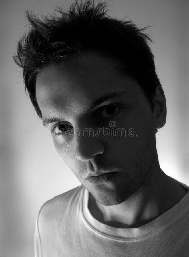 Stern Young Man. A stern looking young man with wild hair and an attitude stares into the face of the viewer like he means business, shot with high contrast royalty free stock photography