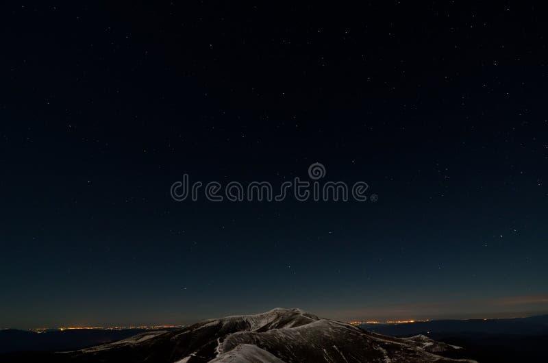 Sterne über schneebedeckten Herbstgebirgskanten lizenzfreies stockbild