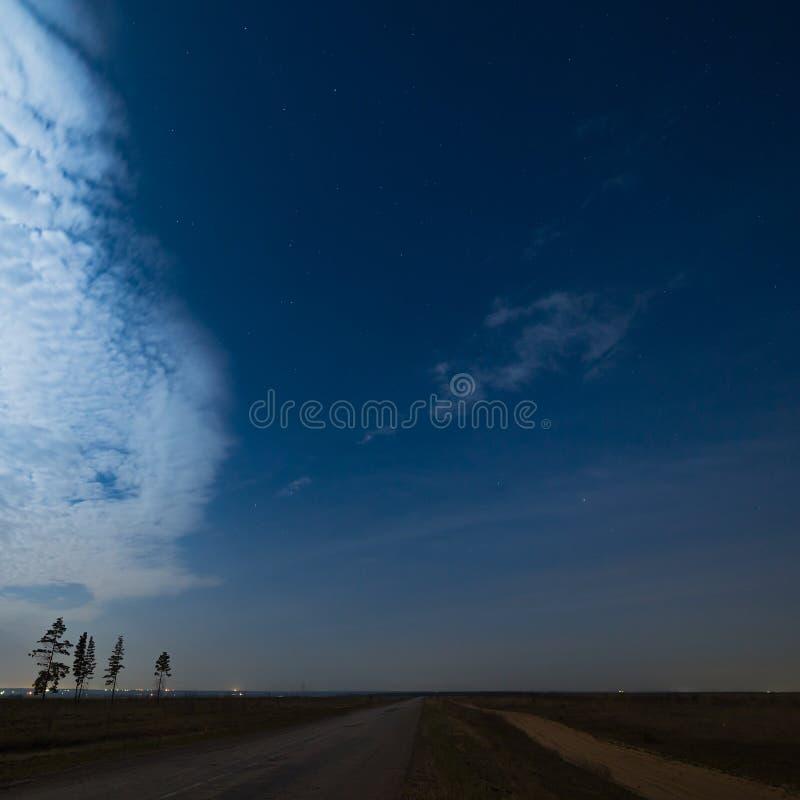 Sterne im nächtlichen Himmel mit Wolken über der Straße Die Landschaft stockfotos