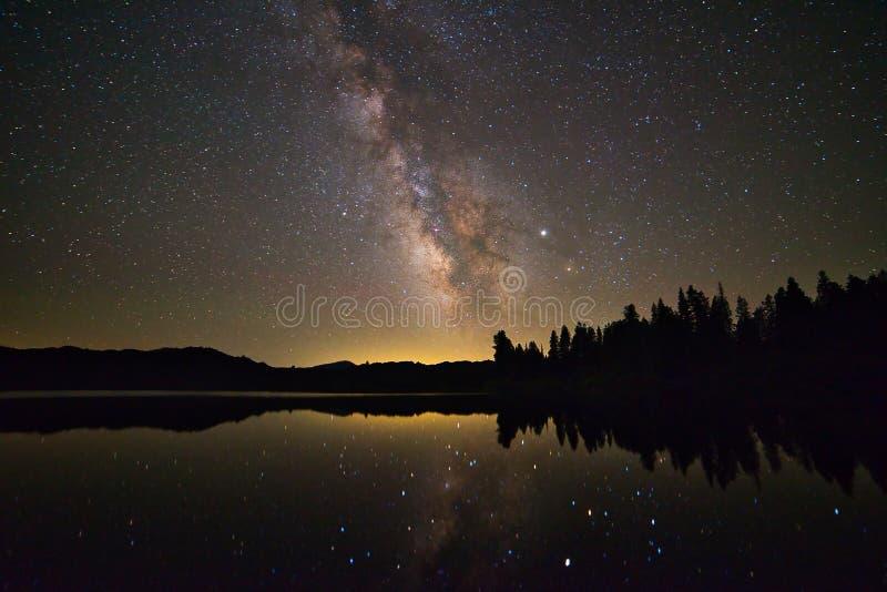 Sternenklaren, glänzenden Milchstraßeflecken über einem See stockbilder
