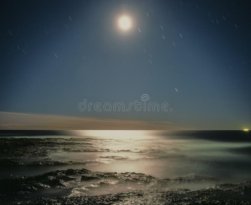 Sternspuren über dem hellen Mond des Pazifischen Ozeans, der auf Wasserlandschaftsfarbnacht Newcastle New South Wales Australien  stockfotografie