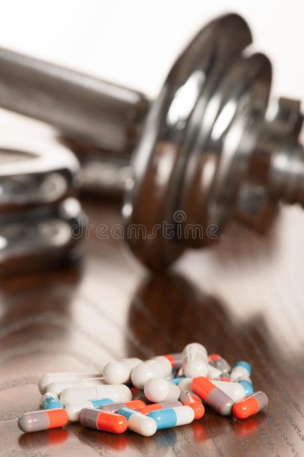 Steroid pills with dumbbell waight in the background - doping in royalty free stock photography