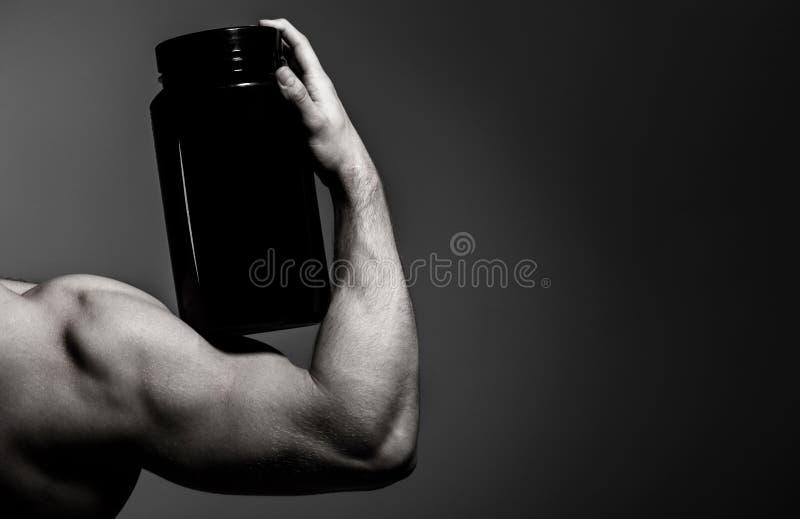 Steroid sportvitamin, dopa som är anabolt, protein Muskulös hand, tricep Stark hand, manarm, muskulös arm för näve royaltyfria foton