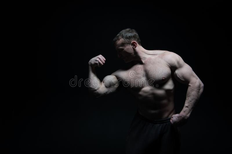 Steroidi anabolizzanti bicipite del muscolo di manifestazione dell'uomo dopo avere usando gli steroidi anabolizzanti steroidi ana immagine stock