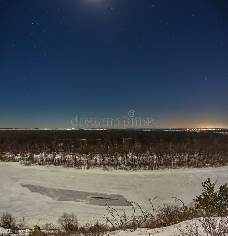 Sterren in de nachthemel De winterlandschap met een bevroren die rivier onder de volle maan wordt gefotografeerd stock foto