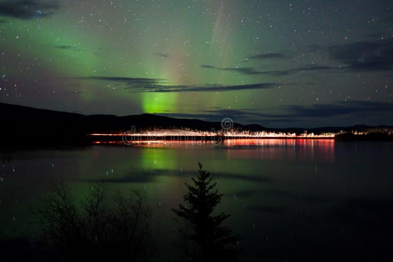 Sterren en Noordelijke Lichten over donkere Weg bij Meer stock foto's
