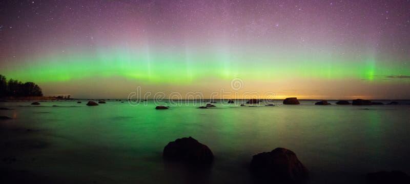 Sterrige hemel en aurora borealis over overzees stock afbeelding