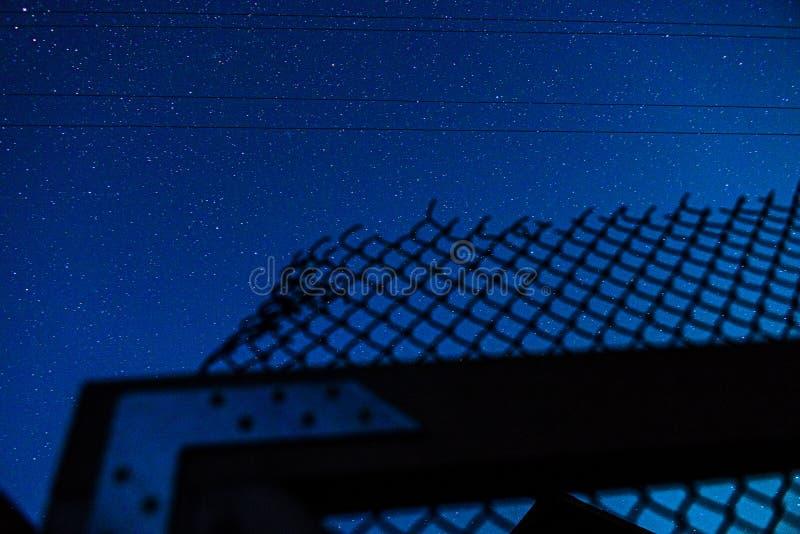 Sterrige hemel en netwerkomheining stock foto's