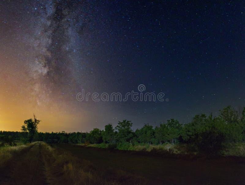 Sterrige hemel met Melkwegmelkweg over het landelijke landschap van de de zomernacht stock fotografie