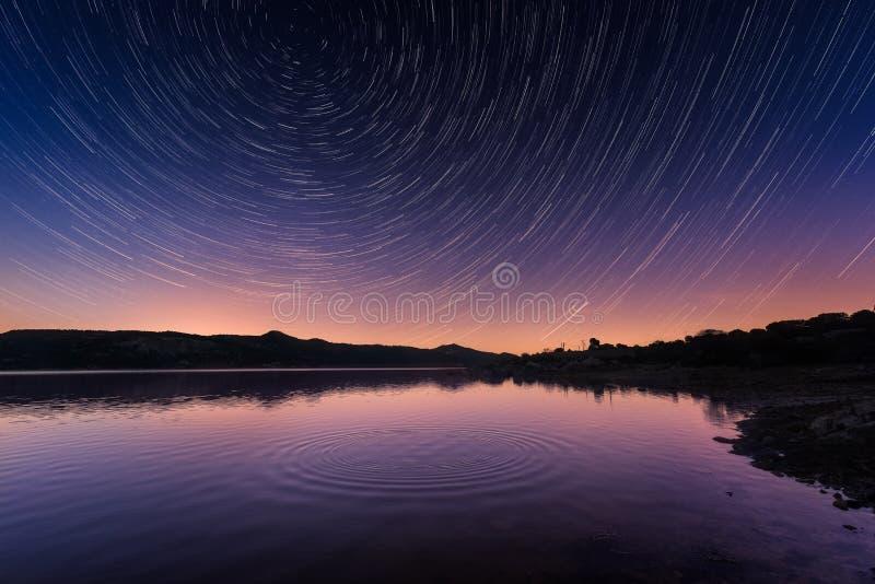 Sterslepen boven rimpelingen op een kalm meer in Corsica bij zonsopgang stock afbeeldingen