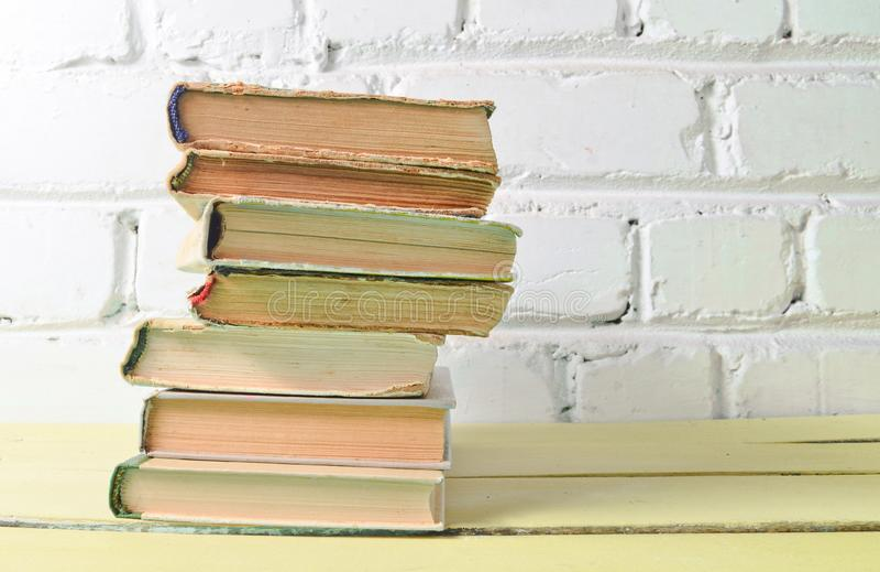 Sterta antyk rezerwuje na stole przeciw białej ścianie z cegieł Szkolny pojęcie, edukacja zdjęcia royalty free