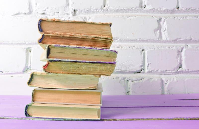 Sterta antyk rezerwuje na stole przeciw białej ścianie z cegieł Szkolny pojęcie, edukacja obrazy stock