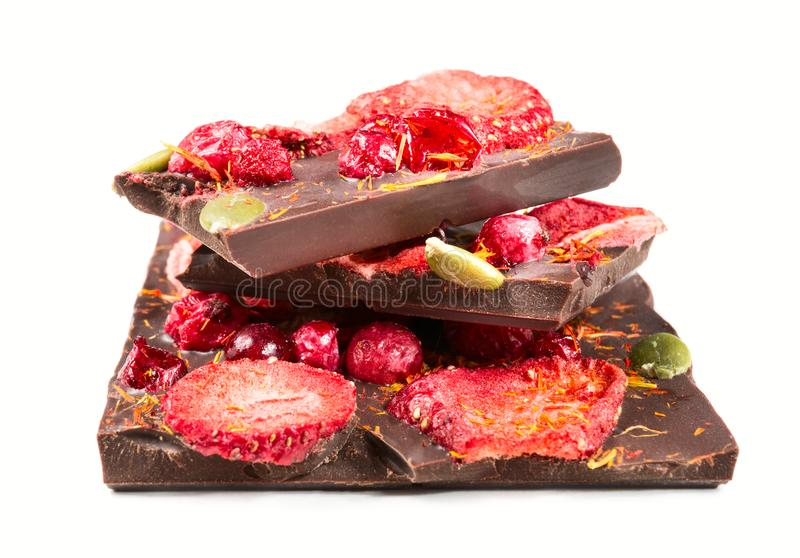 Sterta czekoladowego baru kawałki z wysuszonymi truskawkami i cranberry na białym tle obraz royalty free