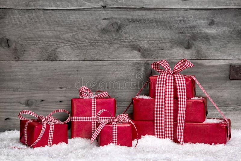 Sterta czerwoni Bożenarodzeniowi prezenty, śnieg na popielatym drewnianym tle.