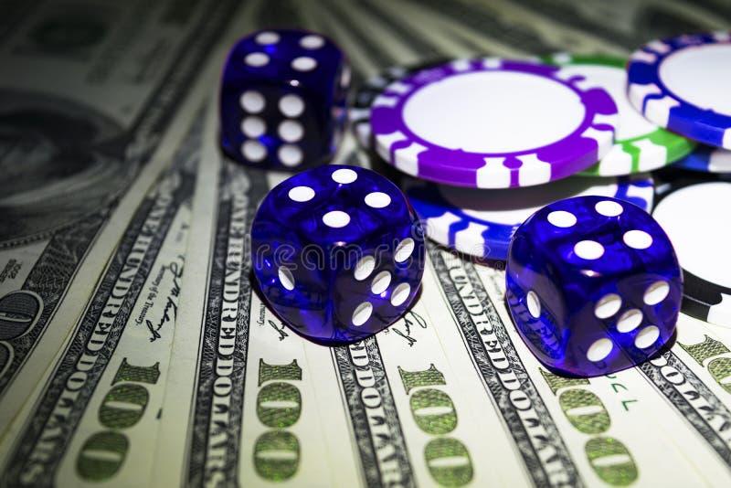Sterta grzebaków układy scaleni z błękitnymi kostka do gry rolkami na dolarowi rachunki, pieniądze Grzebaka stół przy kasynem Par obraz royalty free