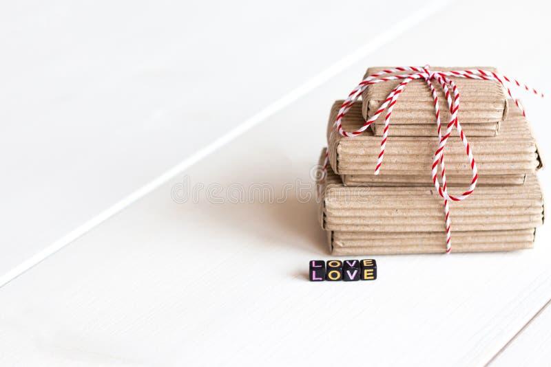 Sterta handcraft prezentów pudełka na białym drewnianym tle z tekst miłością barwioni sześciany Odbitkowa przestrzeń, miejsce dla obraz royalty free
