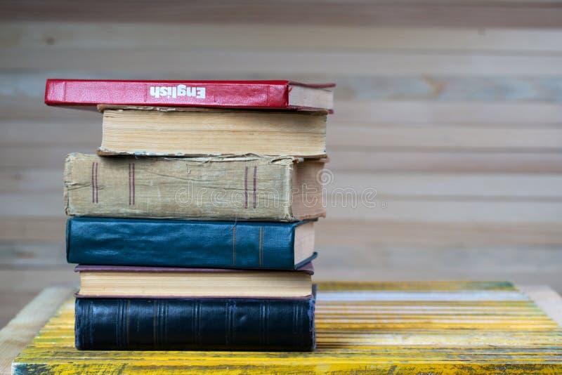 Sterta hardback książki na drewnianym stole Angielski podręcznik zdjęcia royalty free
