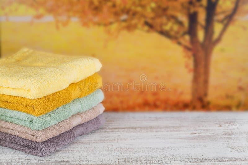 Sterta kolorowi kąpielowi ręczniki na lekkiej drewnianej desce obraz stock