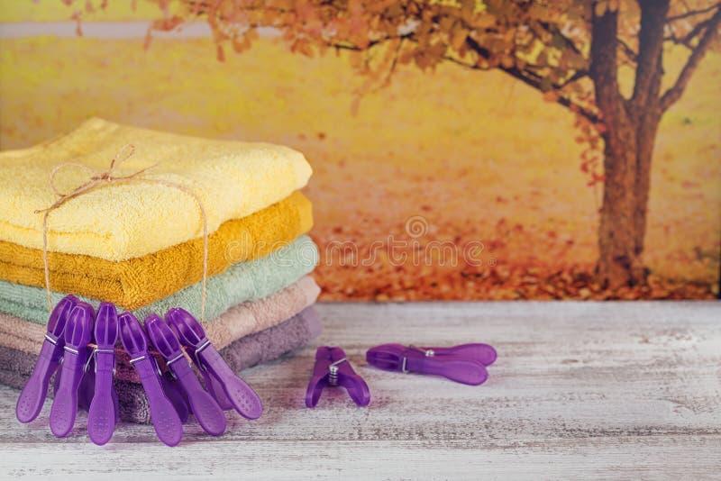 Sterta kolorowi kąpielowi ręczniki na lekkiej drewnianej desce fotografia stock