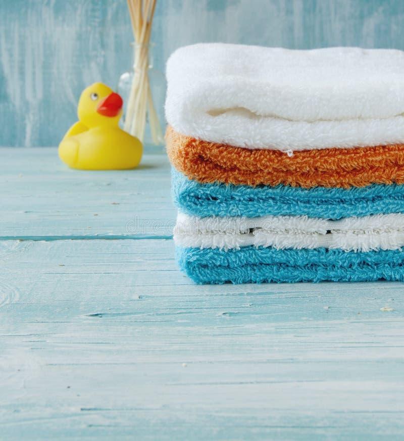 Sterta kolorowi ręczniki i kąpielowa kaczka na stole fotografia stock