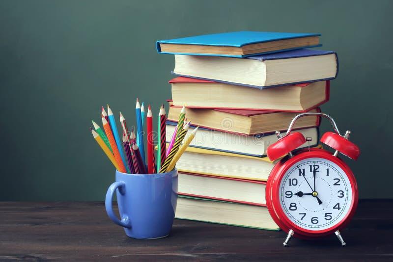 Sterta książki, ołówki i budzik na stole, obraz royalty free
