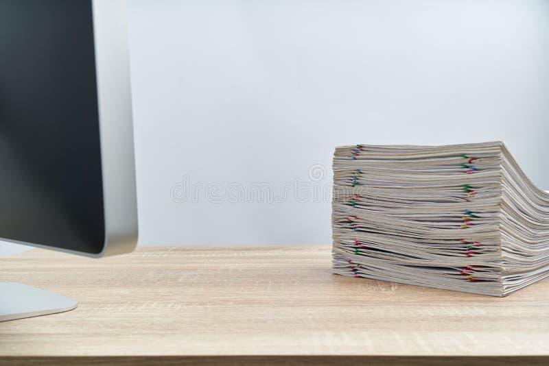 Sterta papierkowej roboty przeciążenia komputer na drewnianym stole i raport zdjęcia stock
