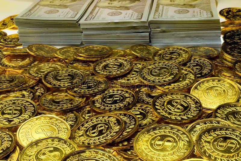 Sterta pliki 100 USA dolarów i złocistych monet banknoty zdjęcie royalty free
