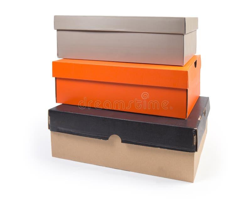Sterta różni zamknięci kartonowi obuwiani pudełka na białym tle fotografia stock