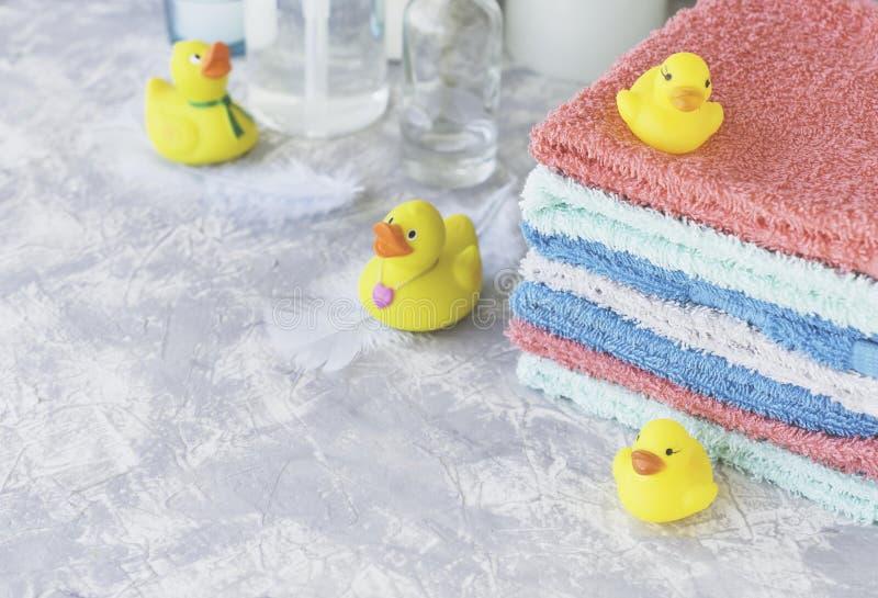 Sterta ręczniki z żółtym gumy skąpaniem nurkuje na bielu marmuru tle, przestrzeń dla teksta, selekcyjna ostrość zdjęcia stock