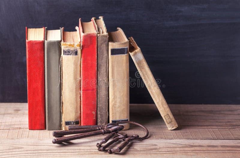 Sterta stary rocznik rezerwuje i wiązka starzy duzi żelazni klucze kłama na drewnianym stole obrazy stock