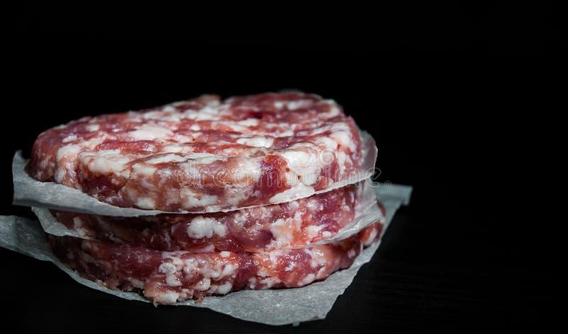 Sterta surowej wołowiny hamburgeru stku cutlets mięsny beefsteack na papierze na ciemnym drewnianym tle fotografia royalty free