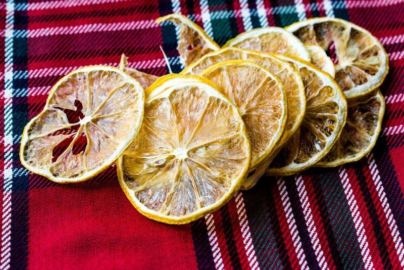 Sterta Wysuszeni cytryna plasterki na Czerwonym Tablecloth, Suchy i Pokrojony/ zdjęcie stock