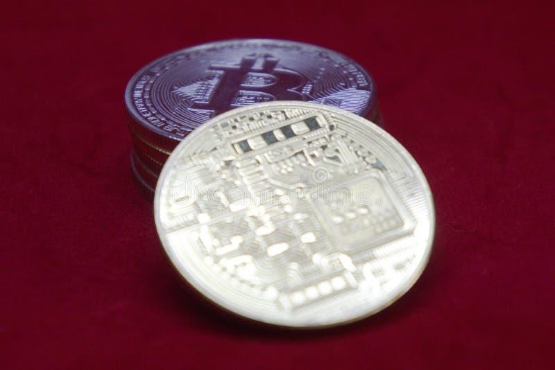 Sterta złota i srebra cryptocurrency monety z bitcoin w przodzie na czerwonym aksamitnym tle zdjęcia stock
