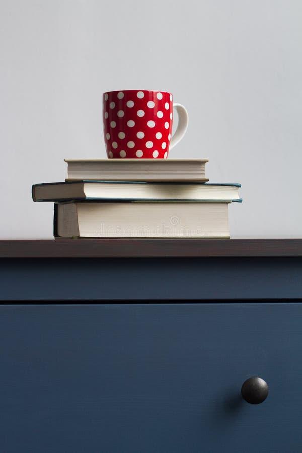 Sterta zamknięte książki z herbacianą filiżanką na wierzchołku na błękitnej klatce piersiowej drawe zdjęcie stock