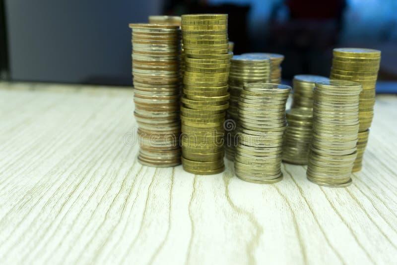 Sterty monety na białego tła różnych wzrostach, zmniejsza dochód biznes obrazy stock