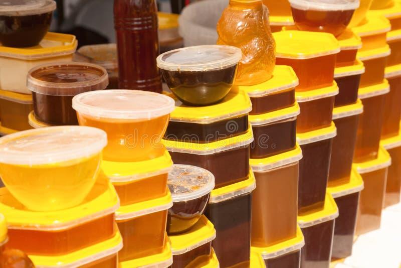 Sterty plastikowi zbiorniki z miodem przy rolnika jedzeniem wprowadzać na rynek obrazy stock