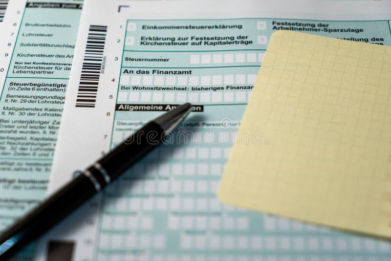 Steuererklaerung mit schwarzem Stift und freiem gelben Zettel version 2 stock photo