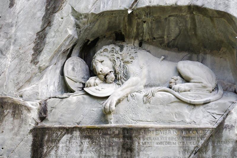 Stervende die Leeuw in rotsachtige muur wordt gesneden royalty-vrije stock afbeelding