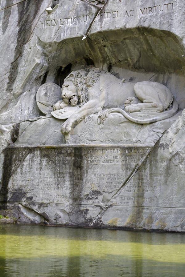Stervende die Leeuw in rotsachtige muur wordt gesneden stock afbeeldingen