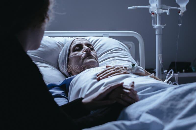 Stervende hogere vrouw met kanker in het ziekenhuisbed met familiesuppo stock fotografie