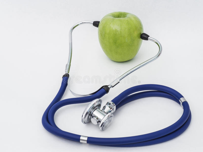 Stethoscope with green apple royalty free stock photography