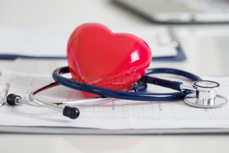 Stethescope und rotes Herz, die auf Kardiogramm liegen lizenzfreie stockfotografie