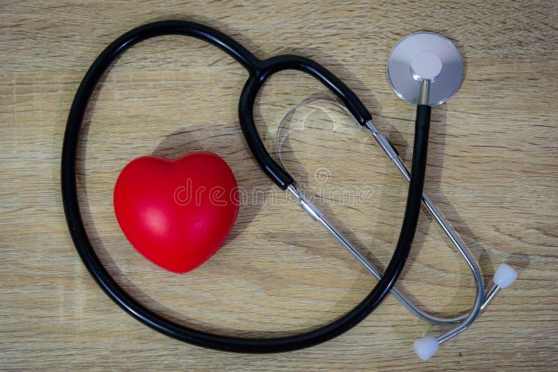 Stethoscoop en rood hart op houten lijst stock afbeeldingen