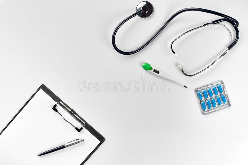 Stethoscoop in het bureau van artsen Hoogste mening van de lijst van het artsen` s bureau, leeg document aangaande klembord met p stock foto