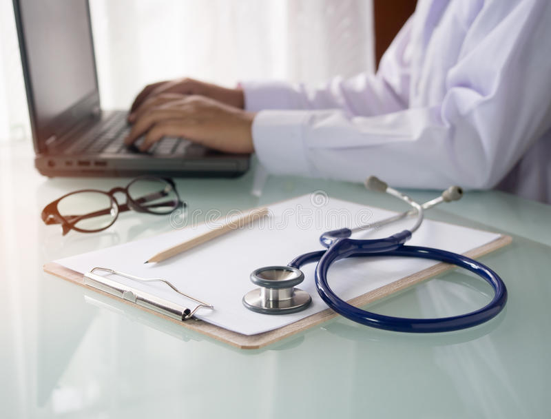 Stethoscoop, klembord en arts die aan laptop werken stock foto's