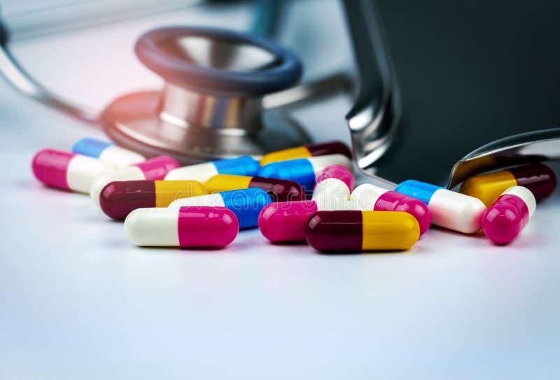Stethoscoop met stapel van kleurrijke antibiotische capsulepillen op witte lijst met drugdienblad Antimicrobial drugweerstand stock foto's