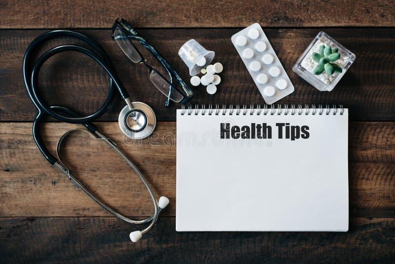 Stethoscoop, oogglas, geneeskunde en notitieboekje met het woord van GEZONDHEIDSuiteinden royalty-vrije stock foto's