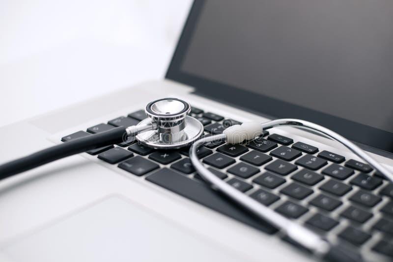 Stethoscoop op een Laptop Computer` s Toetsenbord dat wordt gelegd stock foto's