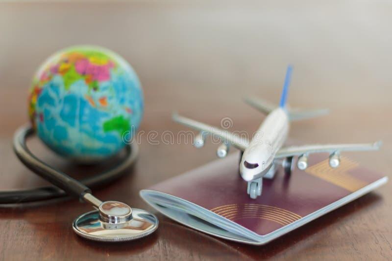 Stethoscoop, paspoortdocument, vliegtuig en bol Gezondheidszorg en reisverzekeringsconcept royalty-vrije stock afbeeldingen