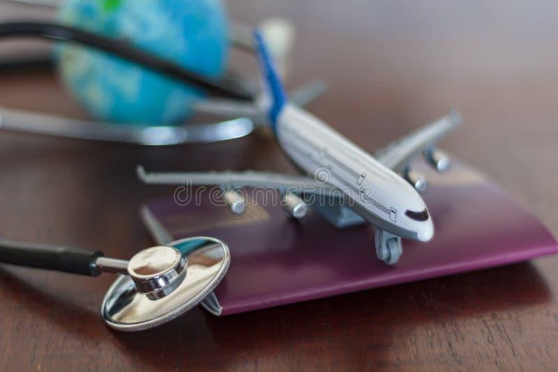 Stethoscoop, paspoortdocument, vliegtuig en bol Globaal Gezondheidszorg en reisverzekeringsconcept stock afbeeldingen